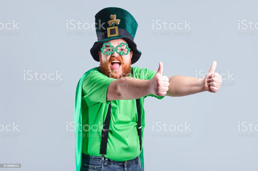 A fat man with a beard in St. Patrick's suit is smiling with a m stock photo