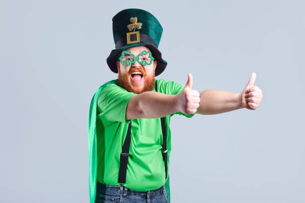 ein dicker mann mit einem bart in st. patricks anzug lächelt mit einem m - bier kostüm stock-fotos und bilder