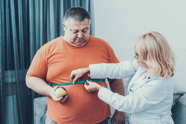 Fat Man with Doctor in White Coat in Gray Room. stock photo