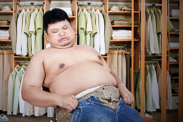 Fat man with his old jeans Obese man trying to wear his old jeans men in tight jeans stock pictures, royalty-free photos & images