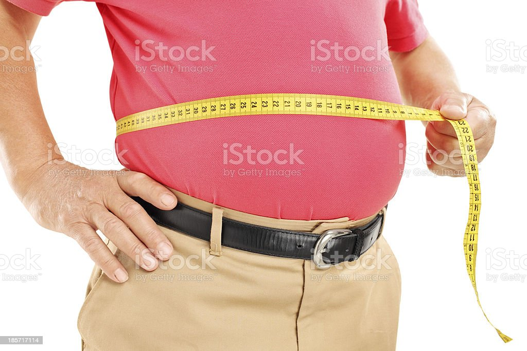 Fat mature man measuring his belly with tape stock photo