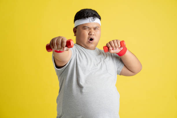 Fat men are exercising by lifting weights. stock photo