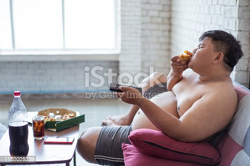 istock Fat men are happy he is watching tvwith eating pizza and soft drinks. 1152025239