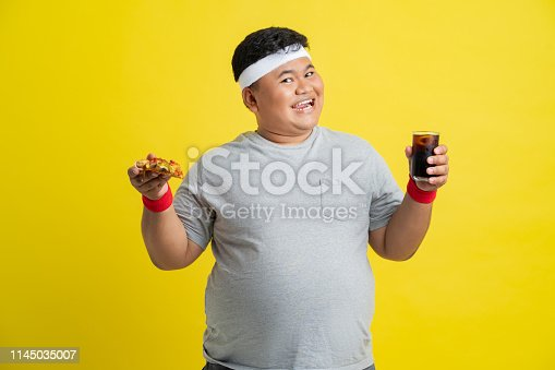 istock Fat men are happy with eating pizza and soft drinks. Before exercise 1145035007
