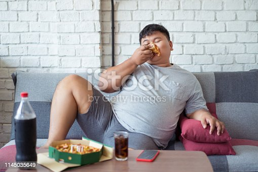 istock Fat men are happy with eating pizza and soft drinks. 1145035649