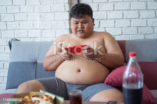 istock Fat men are playing crazy phone games. He eats pizza and soft drinks. 1145035543