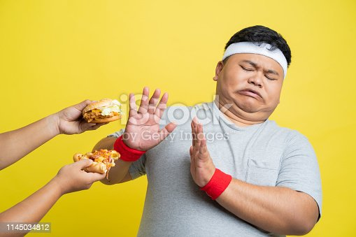istock Fat men refuse to eat pizza and hamburgers. 1145034812