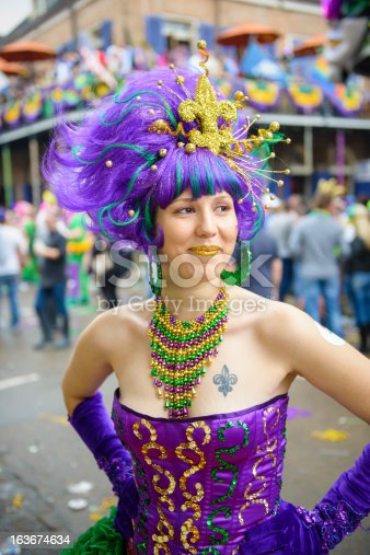 A young woman dressed up on Fat Tuesday on Bourbon Street in New Orleans, LA. The tattoo on her chest is a fleur-de-lis, the symbol of New Orleans.