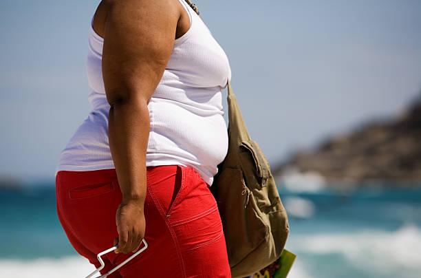 fat frau am strand - damen hosen für mollige stock-fotos und bilder
