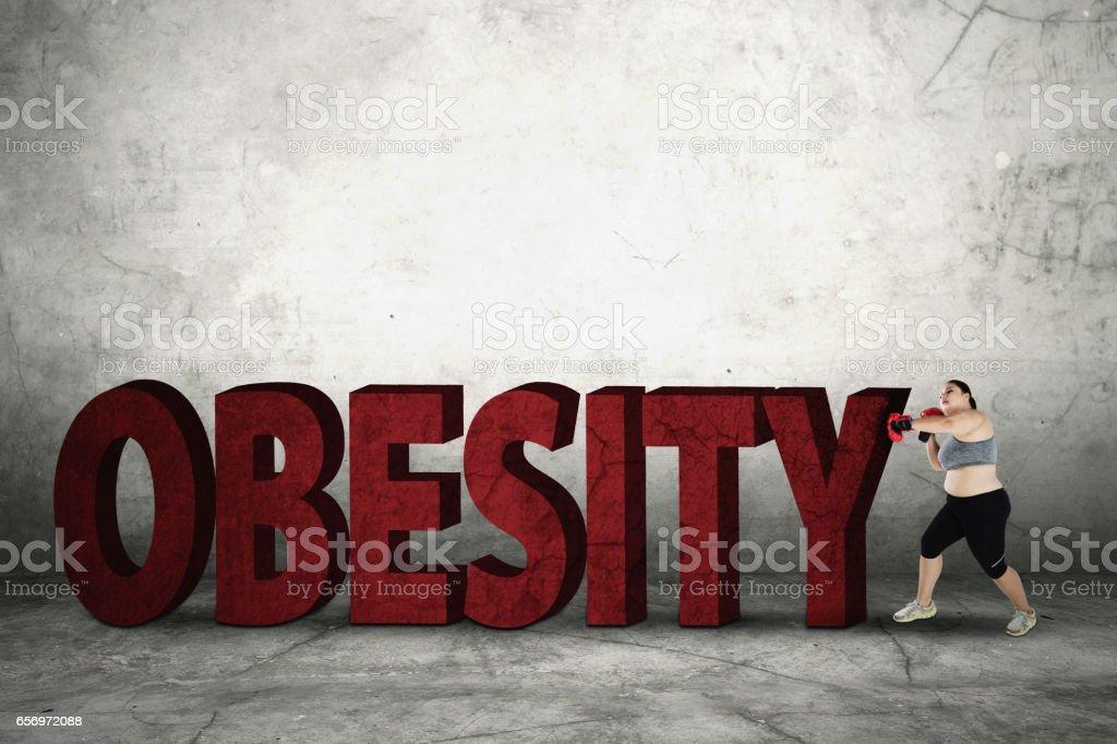 Fat woman crushing obesity word stock photo