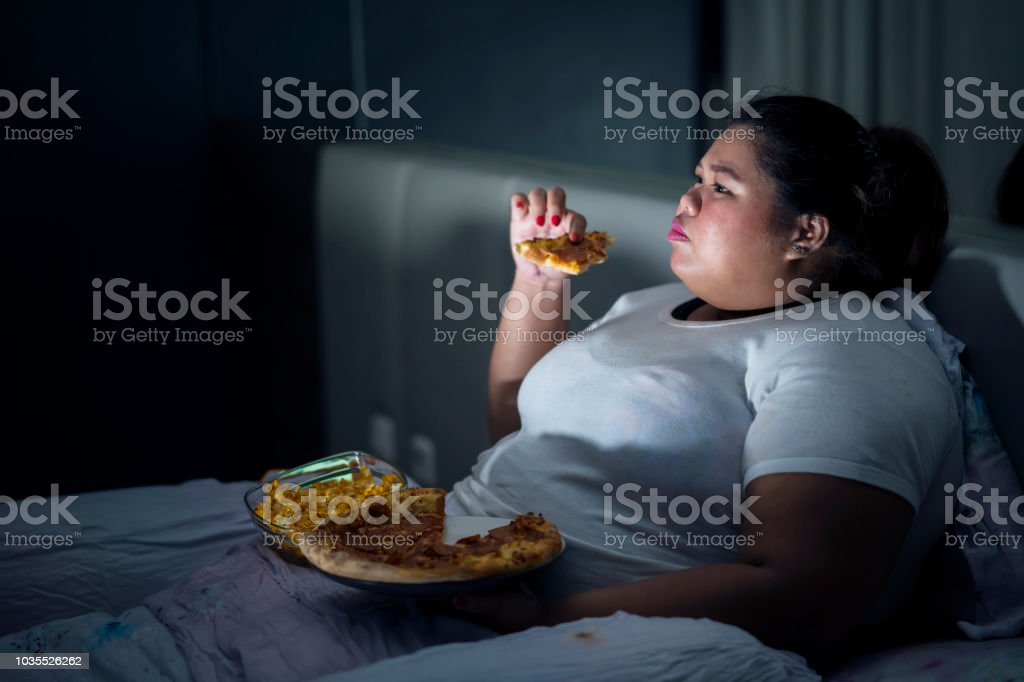 Fat woman eating pizza on bed stock photo