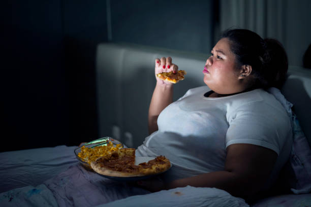 fat woman eating pizza on bed - obesity foto e immagini stock