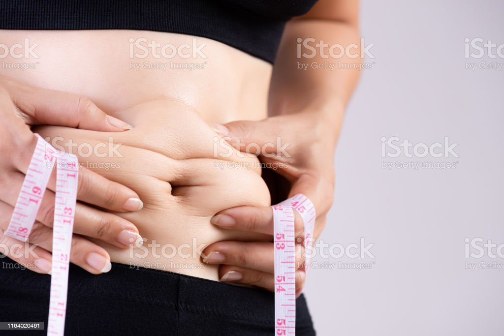 Fat woman hand holding excessive belly fat with measuring tape....