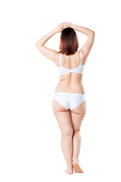 Fat woman in underwear isolated on white background, cellulite on female body stock photo