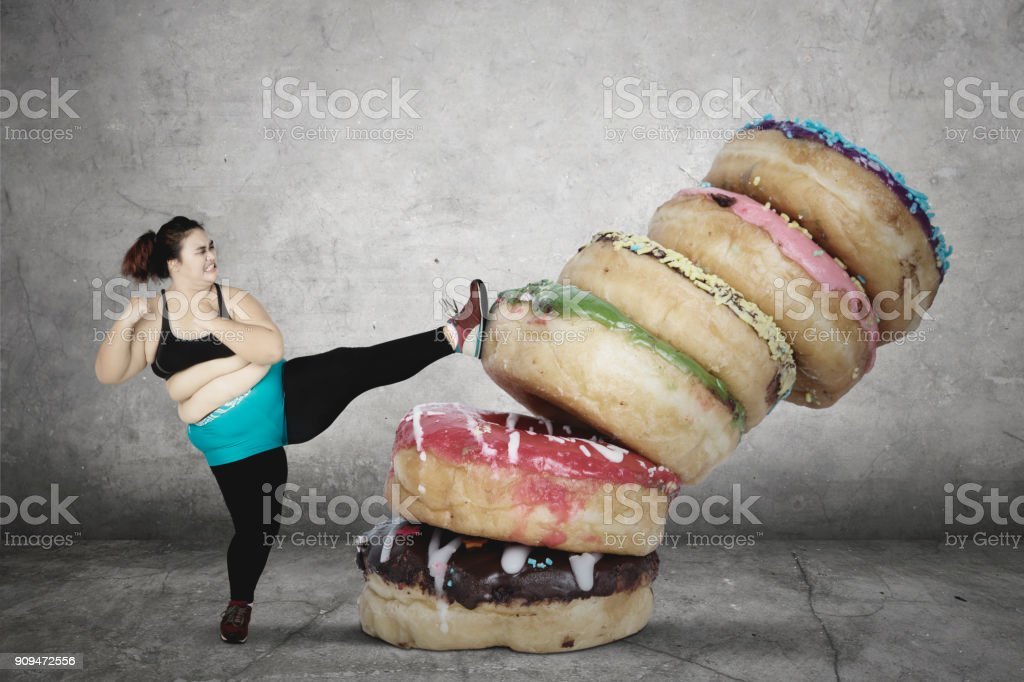 Fat woman kicking a pile of donuts stock photo