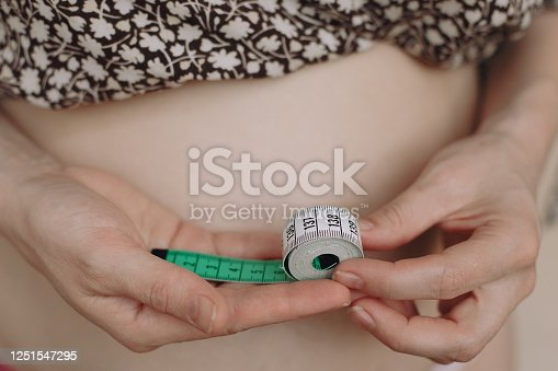 1163494373 istock photo Fat woman measure tape your fat belly on a light background 1251547295