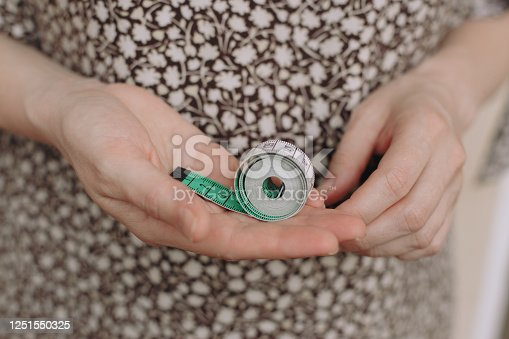 1163494373 istock photo Fat woman measure tape your fat belly on a light background 1251550325