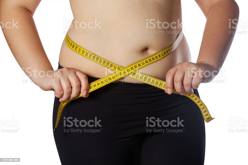 Fat woman measuring her waist with a yellow measuring tape stock photo