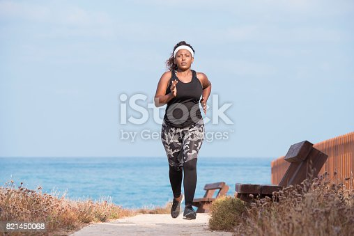 851958232 istock photo Fat woman on morning workout outdoors on the seacoast. 821450068