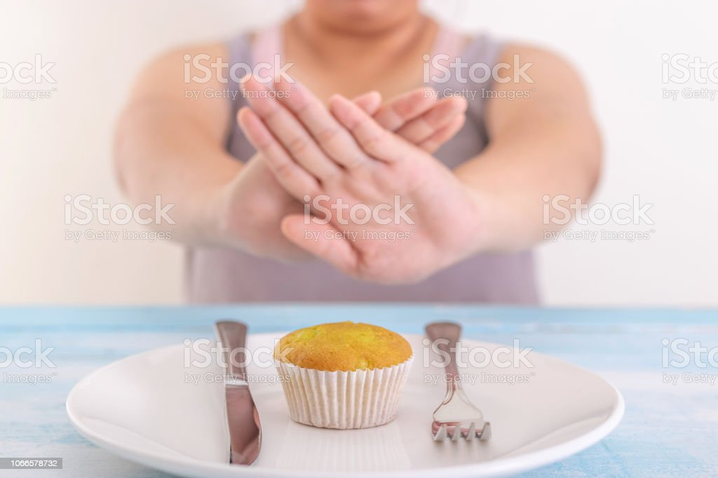 fat woman rejecting cupcake or unhealthy food. Health care concept. stock photo