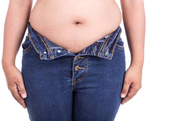 dicke frau versucht zu jeans tragen: fett und gesund-konzept - blähbauch medikamente stock-fotos und bilder