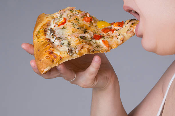 fat woman with a piece of pizza in hand - dikke pizza close up stockfoto's en -beelden