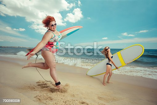 700603062istockphoto Fat woman with the surfboard 700590008