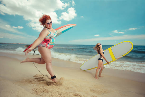 fat woman with the surfboard - funny fat lady stock photos and pictures