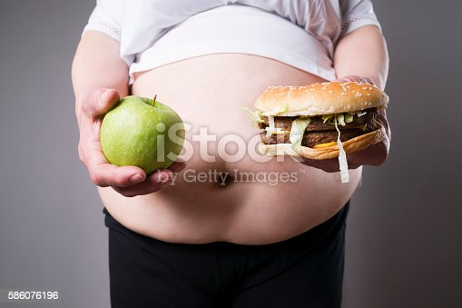 istock Fat women suffer from obesity with hamburger and apple 586076196