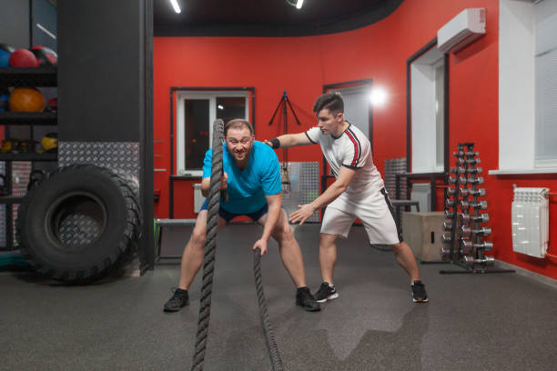 Fat young man is performing battle rope exercise in the fitness gym with the last of his strength under control of his personal coach. Excess weight stock photo