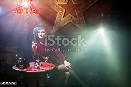 Beautiful young woman dressed in retro dress with retro style accessories is holding the cigarette in mouthpiece in her hand. She is sitting with his legs crossed at the table. A old-fashion telephone and martini glass on the table. The young woman looking directly into the camera. Old cinema projector next to the young woman. The ray of light from a film projector shining into the camera. Studio shooting with smoke