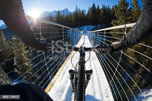The handlebar view of a man riding a fatbike over a suspension bridge in the Rocky Mountains of Canada. Fatbikes are mountain bikes with oversized wheels and tires for riding on the snow.
