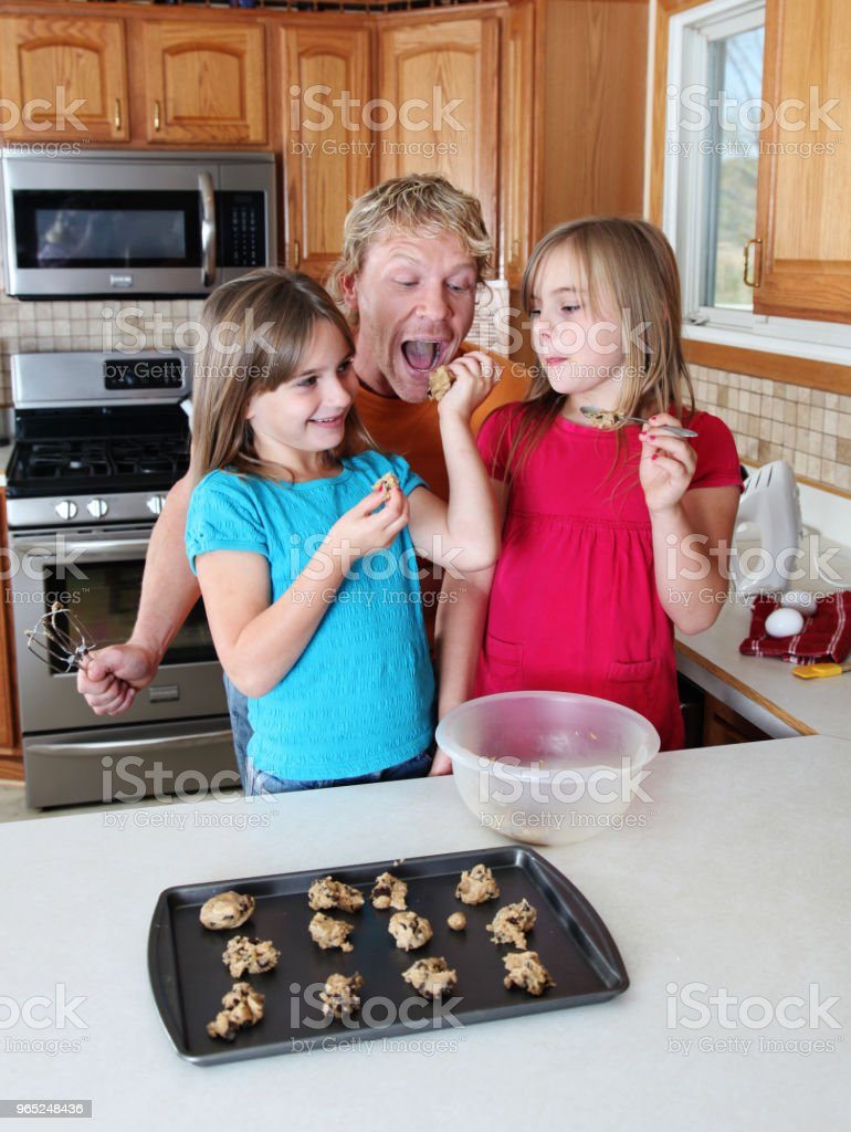 father and 2 young daughters making cookies zbiór zdjęć royalty-free