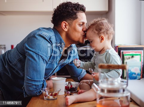 A father and a small toddler son eating fruit and yoghurt in kitchen indoors at home.