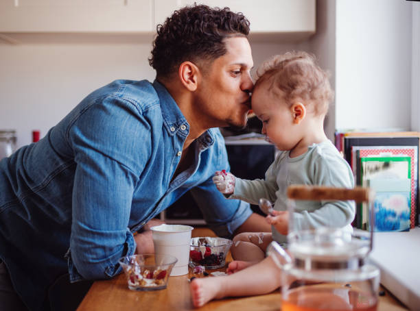 A father and a small toddler son eating fruit and yoghurt indoors at home. A father and a small toddler son eating fruit and yoghurt in kitchen indoors at home. spanish and portuguese ethnicity stock pictures, royalty-free photos & images