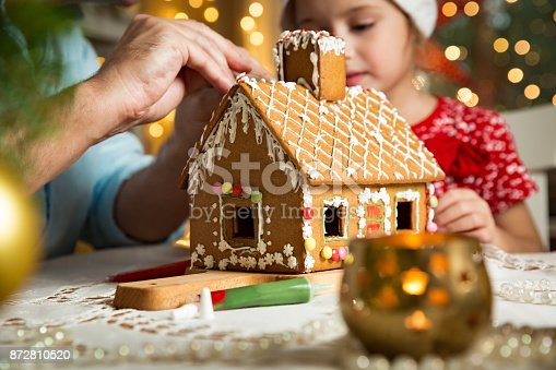 istock Father and adorable daughter in red hat building Christmas gingerbread house 872810520