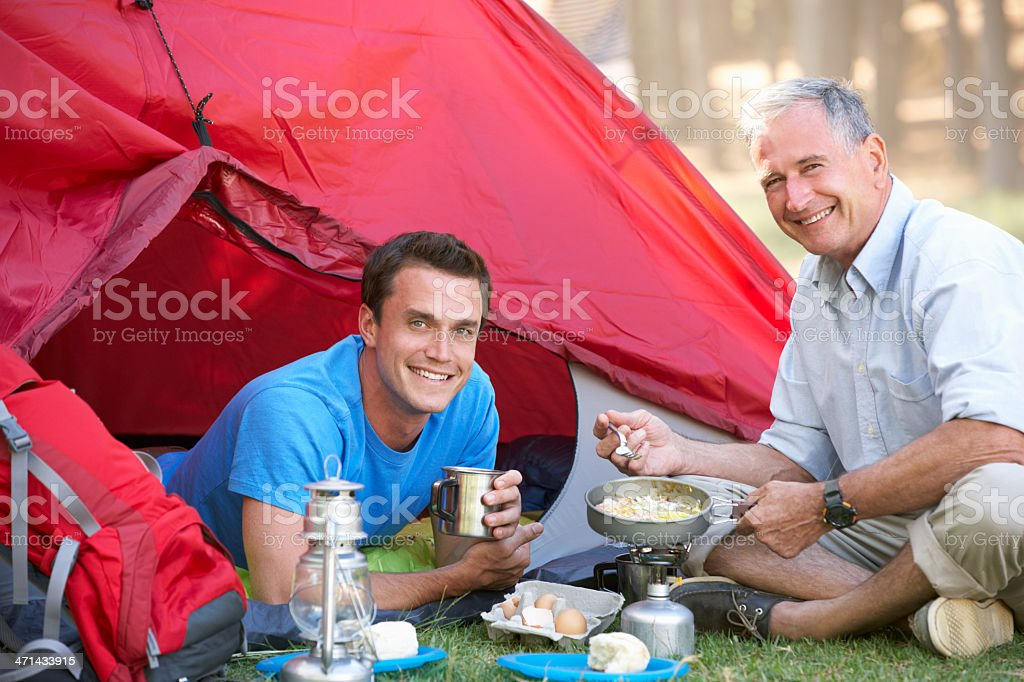 Father And Adult Son Cooking Breakfast On Camping Holiday royalty-free stock photo