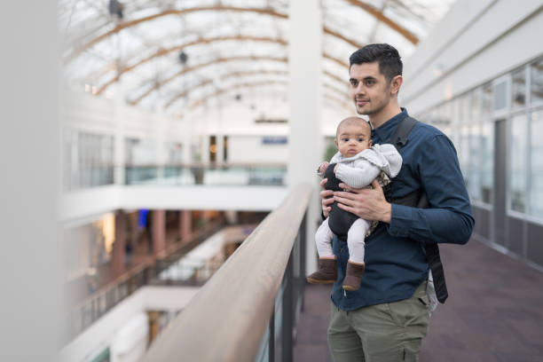 A father and baby exploring a shopping mall stock photo