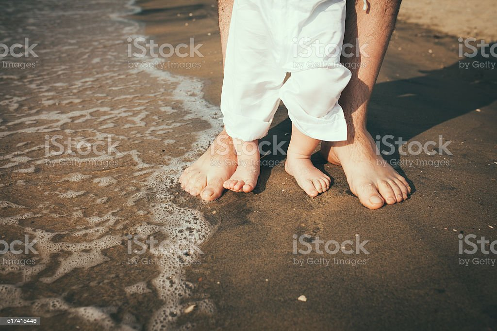 father and baby feet walking on sand beach stock photo