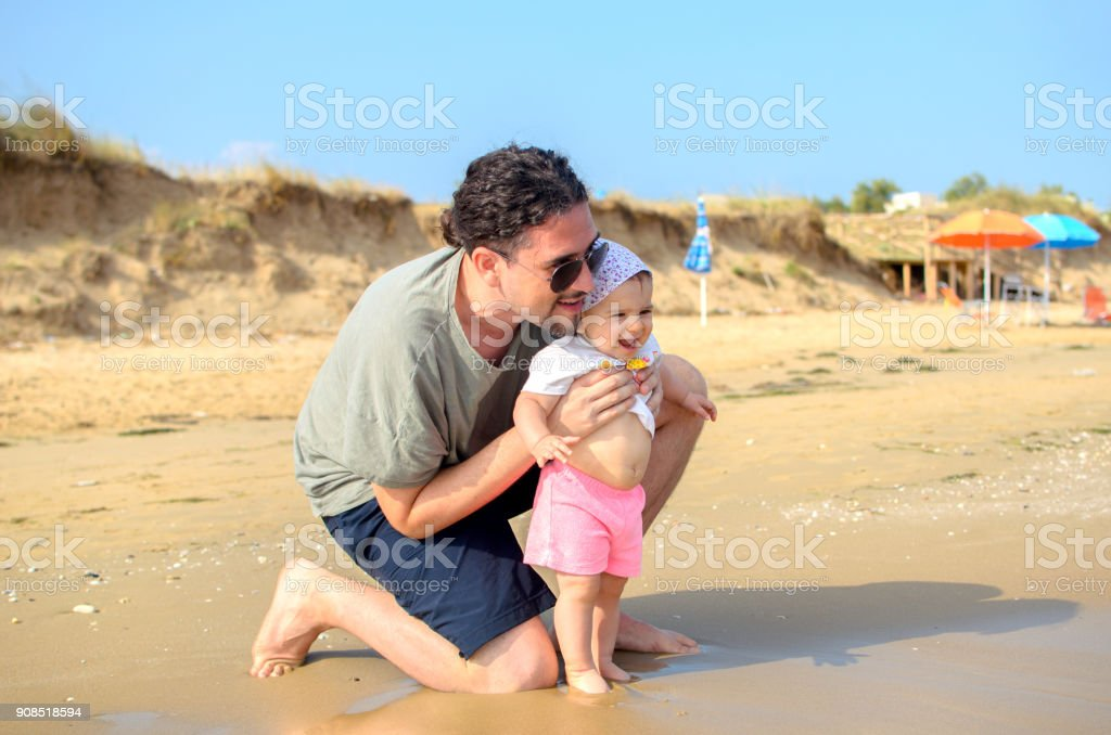 father and baby newborn at the sea shore beach in summer family stock photo