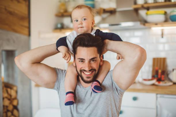 hijo de padre y el bebé pasan mañana en la cama - padre que se queda en casa fotografías e imágenes de stock
