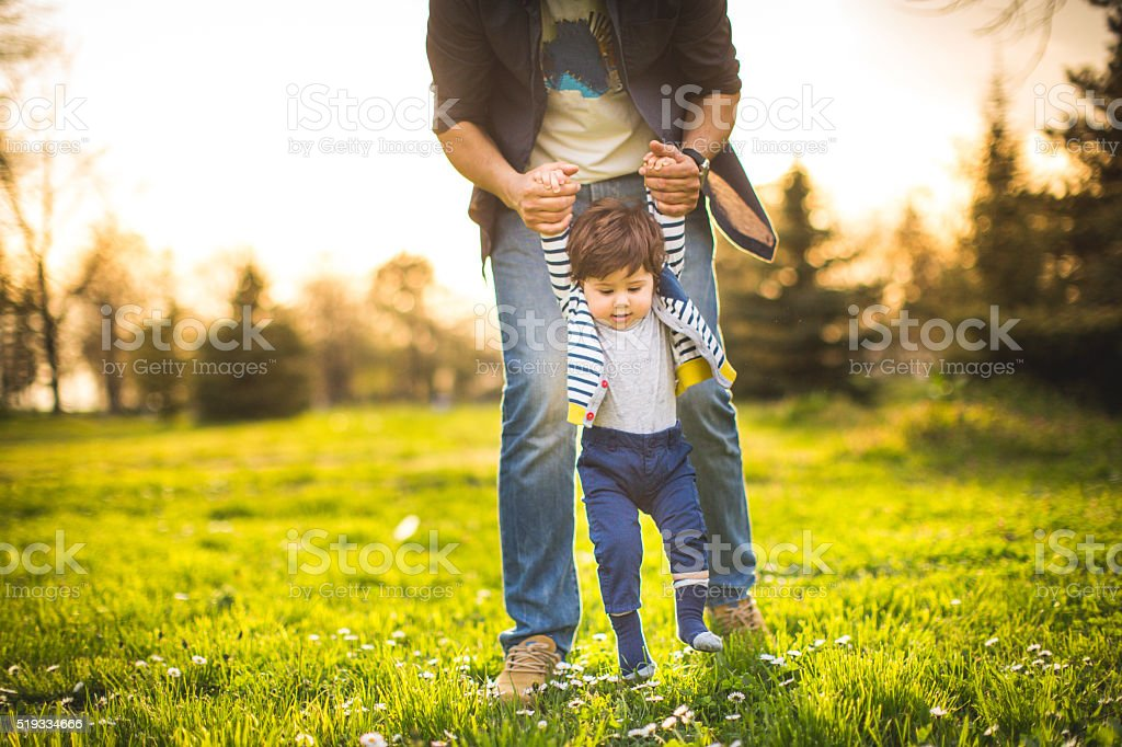 Father and baby spending time together on the grass stock photo