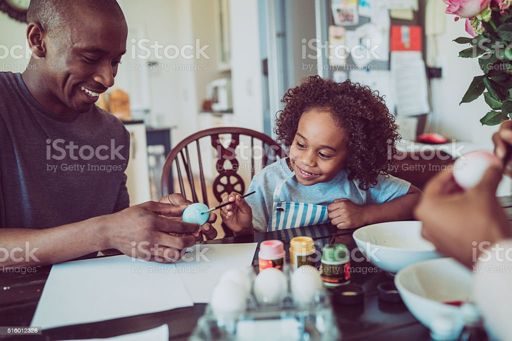 Father and boy colouring Easter egg together stock photo