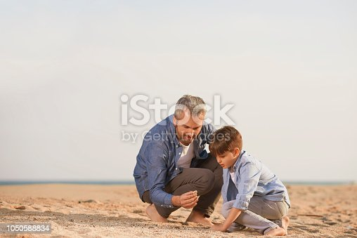 lifestyle shot of young father with his little boy on the beach searching for seashell.
