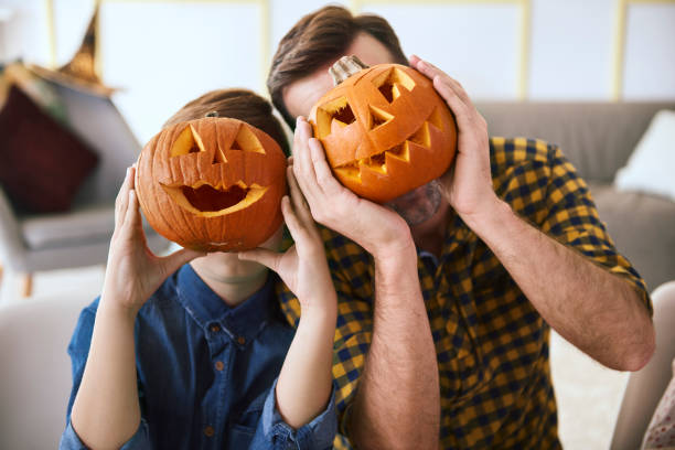 Father and boy with scary Halloween pumpkin Father and boy with scary Halloween pumpkin carving craft product stock pictures, royalty-free photos & images