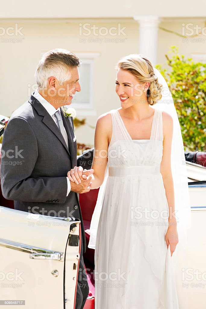 Father And Bride Holding Hands While Standing By Car stock photo