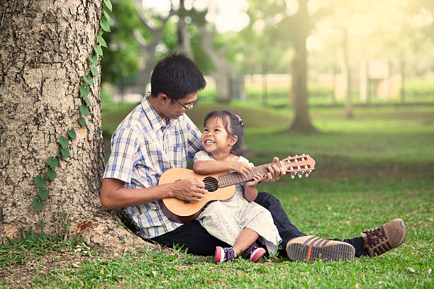 father and child having fun to play guitar together - ukulele songs stock-fotos und bilder