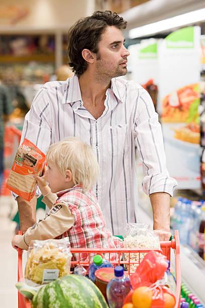 vater und kind im supermarkt - kinder verpackung stock-fotos und bilder