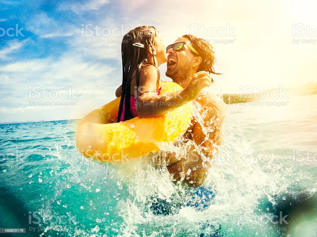 Father and child jumping and having fun together in sea stock photo