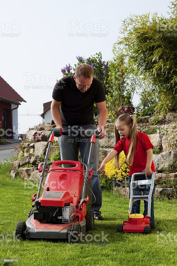 Father and Child mowing the lawn together stock photo